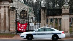 Petugas berjaga di depan gerbang Chesed Shel Emeth Cemetery di University City, St Louis, Missouri, (21/2). Otoritas Missouri sedang menyelidiki dibalik aksi vandalisme ini. (Robert Cohen /St. Louis Post-Dispatch via AP)