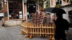 Seorang perempuan berjalan melewati tumpukan kursi dan meja dari bar yang tutup di Brussel, Belgia, Kamis (8/10/2020). Brussels pada Rabu, 7 Oktober 2020, memutuskan menutup semua bar, ruang dansa, dan kafetaria selama sebulan sebagai upaya membendung lonjakan COVID-19. (AP Photo/Francisco Seco)