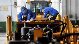 Pekerja menyelesaikan pembuatan buldoser di sebuah pabrik di Zhangjiakou di provinsi Hebei, China Utara (10/4). Umumnya bulldozer banyak digunakan di pekerjaan pertambangan, terutama untuk pertambangan batubara. (AFP Photo/Str/China Out)