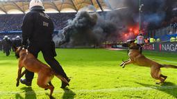 Petugas kepolisian berusaha menenangkan suporter yang mengamuk saat pertandingan antara Hamburg SV melawan VfL Borussia Moenchengladbach di Volksparkstadion, Sabtu (12/5/2018). Hamburg SV terdegradasi dari Bundesliga Jerman. (AP/Michael Sohn)