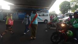 Polwan Polres Jakarta Timur mengenakan kebaya ketika membantu pejalan kaki menyeberang lintas di Jalan Otista Raya, Jatinegara, Jumat (20/4). Para polwan itu berkebaya dalam mengatur lalu lintas untuk memperingati Hari Kartini. (Merdeka.com/Imam Buhori)