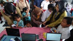 Petugas melakukan scaning jari murid SLB saat tes STIFIn di Sekolah Luar Biasa A Pembina Tingkat Nasional, Lebak Bulus, Jakarta, Selasa (17/12/2019). Tes ini untuk mengetahui minat dan bakat siswa serta merupakan pilot project pertama bagi murid-murid berkebutuhan khusus. (merdeka.com/Arie Basuki)