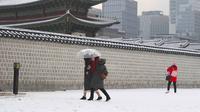 Pengunjung berjalan di istana Gyeongbokgung setelah salju turun di pusat kota Seoul (15/2). Istana ini termasuk dari 5 istana besar dan merupakan yang terbesar yang dibangun oleh Dinasti Joseon.  (AFP Photo/Jung Yeon-je)