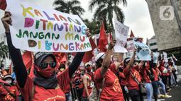 Massa buruh perempuan membentangkan poster tuntutan saat turut dalam aksi menolak UU Cipta Kerja di kawasan Patung Kuda, Jakarta, Selasa (10/11/2020). Dalam aksinya massa buruh mendesak Presiden Jokowi untuk membatalkan UU Cipta Kerja. (merdeka.com/Iqbal S. Nugroho)