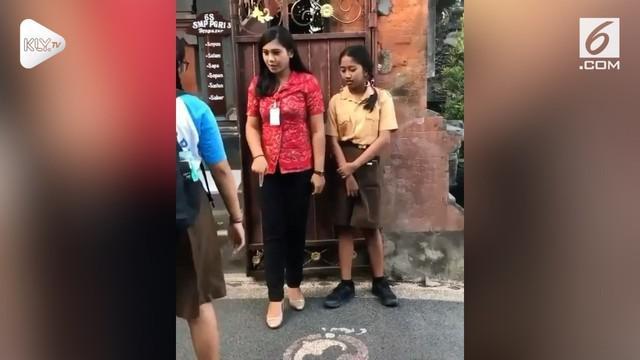 Seorang guru di Bali lakukan sidak kedisiplinan untuk siswanya. Namun kecantikan sang guru tersebut malah membuat warganet ingin dihukum.