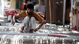 Seorang nelayan Afghanistan membuat jaring yang digunakan untuk mencari ikan di Kalba, Uni Emirat Arab (8/5). Di Kalba ini banyak dihuni oleh warga Afghanistan dan Pakistan yang mencari makan dari hasil laut. (AFP Photo/Karim Sahib)