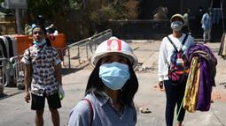 Pengunjuk rasa menggantung pakaian tradisional Myanmar bernama longyi di seberang jalan selama demonstrasi menentang kudeta militer di Yangon, Senin (8/3/2021). Para pengunjuk rasa membentangkan jemuran kain yang biasa dipakai perempuan untuk memperlambat gerak polisi dan tentara. (STR/AFP)