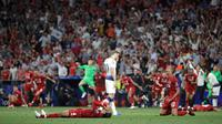 Pemain Tottenham Hotspur Harry Kane berjalan melewati pemain Liverpool yang sedang merayakan kemenangan di final Liga Champions di Stadion Wanda Metropolitano, Madrid, Spanyol, Sabtu (1/6/ 2019). (AP Photo/Felipe Dana)