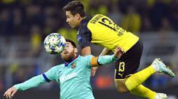 Striker Barcelona, Lionel Messi, duel udara dengan pemain Borussia Dortmund, Raphael Guerreiro, pada Liga Champions di Stadion Signal Iduna Park, Selasa (18/9/2019). Kedua tim bermain imbang 0-0. (AP/Martin Meissner)