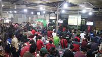 Pendukung Persebaya Surabaya, Bonek, menggelar nonton bersama saat tim kesayangannya menghadapi Tira Persikabo di Stadion Pakansari, Bogor, Sabtu (9/11/2019). Bonek menggelar nonbar karena mendapatkan hukuman dari Komdis PSSI. (Bola.com/Aditya Wany)
