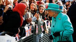 Ratu Elizabeth II menyapa warga saat tiba di pusat perbelanjaan Lexicon saat berkunjung ke Bracknell, London, Jumat (19/10). Ratu Elizabeth menghabiskan sebagian waktu siangnya untuk mengunjungi department store. (HENRY NICHOLLS/ POOL/AFP)