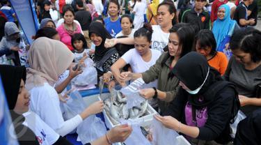Warga menyerbu pasar ikan murah di Pelataran Parkir Sarinah, Thamrin, Jakarta Pusat, Minggu (26/6). Kementerian Kelautan dan Perikanan (KKP) menggelar acara pasar ikan murah dalam rangka kegiatan ramadan. (Liputan6.com/Gempur M Surya)