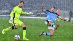 Penyerang Lazio, Ciro Immobile, berusaga merebut bola dari kiper Club Brugge, Simon Mignolet, pada laga Grup F Liga Champions di Olympic Stadium, Rabu (9/12/2020) dini hari WIB. Lazio bermain imbang 2-2 melawan Club Brugge. (AFP/Tiziana Fabi)