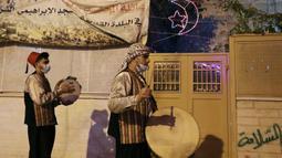 """Pria Palestina yang dikenal dengan """"Musaharatis"""" saat bertugas sebagai """"penabuh drum Ramadhan"""" di kota tua Hebron, Tepi Barat pada 14 April 2021. Membangunkan sahur sudah menjadi tradisi yang sudah mereka lakukan selama Ramadhan. (HAZEM BADER/AFP)"""