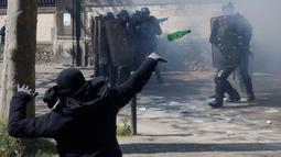 Seorang pemuda melempar botol ke arah polisi anti huru-hara ketika aksi protes rancangan UU ketenagakerjaan Prancis selama peringatan May Day 2016 atau Hari Buruh Sedunia di Paris , Minggu (1/5). (REUTERS/Philippe Wojazer)