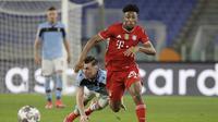 Gelandang Bayern Munich, Kingsley Coman (depan) lolos dari hadangan bek Lazio, Patric dalam laga leg pertama babak 16 besar Liga Champions 2020/21 di Olimpico Stadium, Selasa (23/2/2021). Bayern Munich menang 4-1 atas Lazio. (AP/Gregorio Borgia)