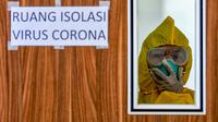Petugas mengenakan peralatan pelindung di ruang isolasi di rumah sakit Undata, Palu, Sulawesi Tengah, Sabtu (1/2/2020). Pemerintah Indonesia bersiap memulangkan sekitar 250 warga dari Wuhan, tim evakuasi diberangkatkan dari Bandara Soekarno Hatta, pada Sabtu (1/2) siang. (AFP/Muhammad Rifki)