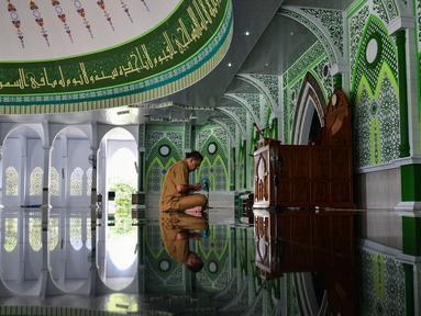 Seorang pria berdoa usai menunaikan salat selama bulan Ramadan di masjid Al Munawarah di Jantho, provinsi Aceh (12/5/2020). Masjid Al Munawarah yang berdiri di pusat Kota Jantho, Kabupaten Aceh Besar dikelilingi oleh perbukitan Bukit Barisan. (AFP/Chaideer Mahyuddin)