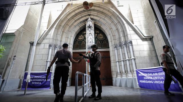 Personel Gegana dan K9 Polda Metro Jaya berdiri di depan pintu Gereja Katedral saat melakukan penyisiran, Jakarta, Minggu (24/12). Sterilisasi ini dilakukan untuk menjamin rasa aman umat kristiani saat menjalankan ibadah Natal.(Liputan6.com/Faizal Fanani)