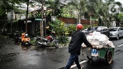 Pemulung melintas di depan kediaman Ihsan Yunus saat digeledah KPK di kawasan Kayu Putih, Pulogadung, Jakarta, Rabu (24/2/2021). Dalam penggeledahan tersebut KPK mengerahkan 10 penyidik dan membawa dua koper saat keluar dari kediaman Ihsan Yunus. (merdeka.com/Iqbal S. Nugroho)