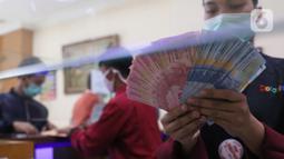 Petugas menunjukkan mata uang rupiah di penukaran uang di Jakarta, Senin (9/11/2020). Rupiah dibuka di angka 14.172 per dolar AS, menguat jika dibandingkan dengan penutupan perdagangan sebelumnya yang ada di angka 14.210 per dolar AS. (Liputan6.com/Angga Yuniar)