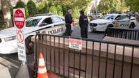 Petugas Secret Service berbincang di pos pemeriksaan dekat rumah mantan Presiden AS, Barack Obama di Washington, Rabu (24/10). Dinas Rahasia AS telah menggagalkan pengiriman paket berisi bahan peledak ke rumah Barack Obama. (AP /Alex Brandon)