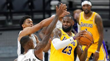 Pebasket Los Angeles Lakers, LeBron James, berebut bola dengan pebasket San Antonio Spurs, Lonnie Walker dan Keldon Johnson pada laga NBA di AT&T Center, Kamis (31/12/2020). LA Lakers menang dengan skor 121-107. (AP/Eric Gay)