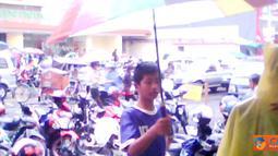 Citizen6, Tasikmalaya: Seorang anak sedang berusaha menawarkan payung untuk digunakan pejalan kaki.
