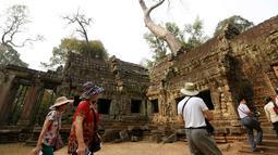 Wisatawan mengunjungi kompleks kuil Ta Prohm di provinsi Siem Reap, Kamboja. Dengan membiarkan lilitan akar pohon besar memeluk tubuh candi inilah keunikan yang menjadikan Ta Phrom salah satu candi paling banyak dikunjungi wisatawan. (REUTERS/Samrang Pring)