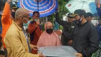 Pelaksana Tugas Wali Kota Bengkulu Dedy Wahyudi menyerahkan bantuan terpak kepada warga yang terkena musibah angin puting beliung. (Liputan6.com/Yuliardi Hardjo)