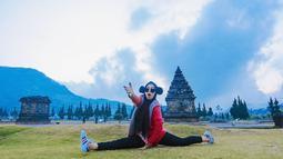Gadis kelahiran Batam ini merentangkan kedua kakinya dan menunjukkan ekspresi yang lucu saat liburan di Dieng. Dengan pakaian serba hitam, ditambah dengan jaket merah dan sepatu putih, ia berpose di depan sebuah bangunan candi. (Liputan6.com/IG/@riaricis1795)
