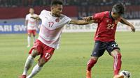 Gelandang Indonesia, Saddil Ramdani, berebut bola dengan pemain Laos, Phithack Kongmathilath, pada laga Asian Games di Stadion Patriot, Jawa Barat, Jumat (17/8/2018). Indonesia menang 3-0 atas Laos. (Bola.com/Peksi Cahyo)