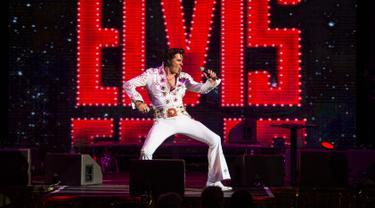 Seorang penyanyi, Jason Dale tampil dalam pembukaan 'Perayaan Elvis 2018' di Blackpool Winter Gardens, Barat Laut Inggris, Jumat (29/6). Festival ini digelar untuk memperingati penyanyi legendaris Elvis Presley. (Oli SCARFF/AFP)