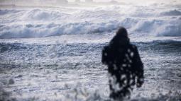 Seorang pria melihat kota Penmarch dari pantai La Torche di Plomeur, Prancis barat (28/12/2020). Badai Bella pun dilaporkan menyebabkan gangguan pada perjalanan udara. (AFP/Loic Venance)