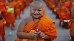 Seorang Biksu Buddha tersenyum saat menunggu acara penerimaan sedekah di kuil Wat Phra Dhammakaya, Bangkok, Thailand, (22/4). Kegiatan ini juga sebagai penasbihan para bhikkhu dan samanera atau calon Biksu. (REUTERS / Jorge Silva)