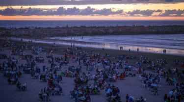 Warga buka puasa bersama keluarga dan kerabat sambil menikmati matahari terbenam di pantai Rabat, Maroko (9/6). Selama Ramadan, banyak warga Maroko berkunjung ke pantai menikmati angin Atlantik dan menikmati pemandangan laut. (AP Photo/Mosa'ab Elshamy)
