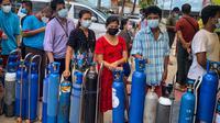 Orang-orang antre menunggu di lokasi yang menyumbangkan oksigen secara gratis di Yangon, Myanmar pada 14 Juli 2021. Mereka putus asa mencari oksigen untuk menjaga orang yang dicintai tetap bernapas ketika gelombang corona covid-19 menerjang negara yang dilanda kudeta itu. (Ye Aung THU/AFP)