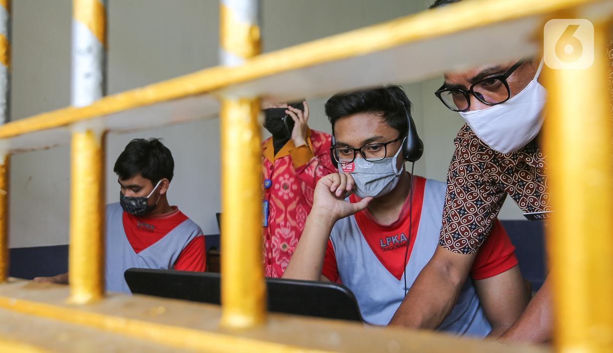 Anak binaan dibantu pegawai lapas anak tengah menyiapkan komunikasi virtual dengan keluarganya di Lembaga Pembinaan Khusus Anak (LPKA) Klas 1 Tangerang, Banten, Sabtu (30/5/2020). Fasilitas yang diberikan LPKA dilakukan karena tidak ada kunjungan selama pandemi Covid-19. (Liputan6.com/Fery Pradolo)