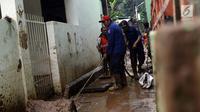 Petugas Damkar PB membersihkan lumpur sisa banjir di salah satu gang di kawasan Rawajati, Jakarta, Sabtu (27/4). Banjir akibat luapan air sungai Ciliwung sempat melanda kawasan ini pada Jumat (26/4). (Liputan6.com/Helmi Fithriansyah)