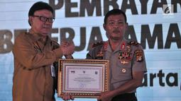 Mendagri Tjahjo Kumulo memberikan penghargaan kepada Kapolda Metro Jaya Irjen Pol Idham Aziz saat peresmian Samsat Digital dan Pembayaran Non Tunai di Jakarta, Senin (26/3). Sistem ini hasil kerja sama dengan Bank DKI. (Merdeka.com/Iqbal Nugroho)