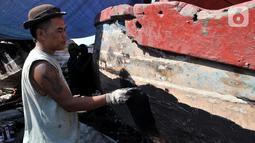 Pekerja menyelesaikan proses perbaikan kapal nelayan di pesisir Marunda, Jakarta, Selasa (22/10/2019). Untuk jasa perbaikan satu buah kapal biasanya dipatok dengan harga Rp 15 juta dalam waktu pengerjaan hingga sebulan. (merdeka.com/Iqbal Nugroho)