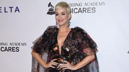 Penyanyi Katy Perry tersenyum saat berpose menghadiri pesta Gala Musicares Person of The Year 2019 di Los Angeles (8/2). Katy Perry tampil menawan mengenakan gaun hitam bermotif kembang dengan belahan hingga paha terbuka. (AFP Photo/Valerie Macon)