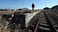 Wisatawan mengamati Stasiun Tomioka yang ditinggalkan di Namie, Prefektur Fukushima, 11 Februari 2016. Lima tahun pasca bencana nuklir yang dipicu gempa dan tsunami Jepang, banyak wisatawan yang bergabung dengan tur Fukushima (AFP PHOTO/Toru Yamanaka)