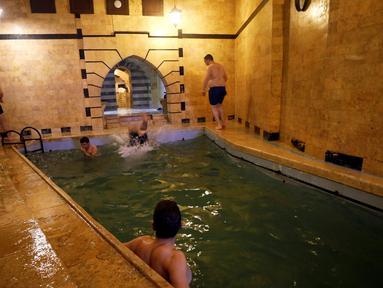 Pengunjung pria berenang di kolam yang ada di pemandian umum Bab al-Ahmar Aleppo pada 11 April 2019.  Warga Suriah menghidupkan kembali tradisi mingguan mereka mengunjungi pemandian umum setelah perang selama bertahun-tahun yang melanda negara tersebut. (REUTERS/Omar Sanadiki)
