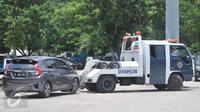 Petugas Dishub DKI Jakarta menderek mobil yang terkena razia parkir liar di penampungan derek parkir liar, Monas, Jakarta, Senin (13/3). Pada periode Januari-Febuari, Dishub menindak 6.437 kendaraan dengan sanksi ditilang. (Liputan6.com/Yoppy Renato)