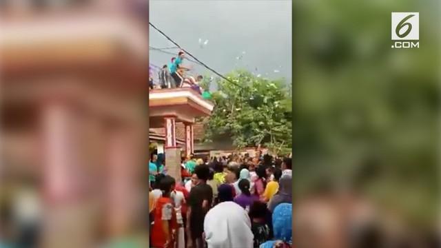 Beredar video sebuah keluarga yang menyebar uang dari atas rumahnya berlantai dua di Probolinggo. Mereka silih berganti melemparkan lembaran uang kertas.