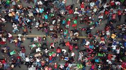 Rombongan imigran Amerika Tengah tujuan Amerika Serikat beristirahat setelah polisi federal menghalangi mereka untuk menyeberangi jembatan antara Chiapas dan Oaxaca di luar Kota Arriaga, Meksiko, Sabtu (27/10). (AP Photo/Rodrigo Abd)