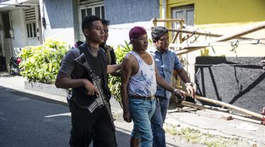 Petugas kepolisian mengamankan seorang pria mencurigakan di sekitar Mapolrestabes Surabaya, Jawa Timur, Senin (14/5). Sebelumnya, bom bunuh diri terjadi sekitar pukul 08.50 WIB di depan markas penjagaan Mapolrestabes Surabaya. (AFP/JUNI KRISWANTO)