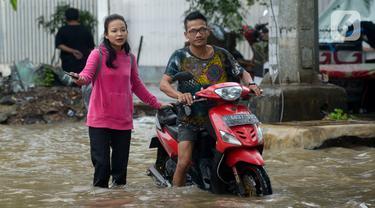 Pengendara sepeda motor menerjang banjir yang merendam Jalan Ahmad Yani, Jakarta, Sabtu (8/2/2020). Hujan yang mengguyur Jakarta sejak semalam membuat sejumlah ruas jalan terendam banjir. (merdeka.com/Imam Buhori)
