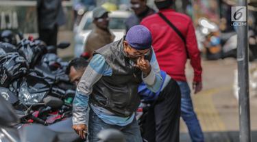 Warga menggunakan odol diwajah untuk menghindari sisa gas air mata pasca bentrok massa dengan aparat di Palmerah, Jakarta, Kamis (26/9/2019). Banyak masyarakat yang melintas dan warga sekitar perih pada mata hingga bersin akibat sisa gas air mata pasca bentrokan kemarin. (Liputan6.com/Faizal Fanani)